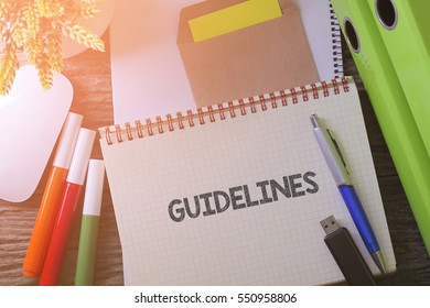 """Notebook writing """"GUIDELINES"""" on table with Working space at the office with plant, usb drive and glasses"""