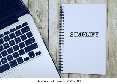 "Notebook writing ""SIMPLIFY"" on table with Working space at the office with laptop."