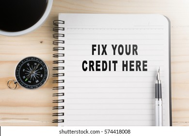 Notebook written with FIX YOUR CREDIT HERE word on wooden background. Business Concept.