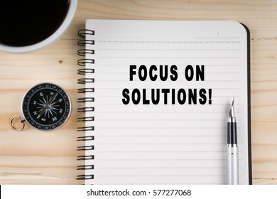 Notebook written with Focus on solutions! word on wooden background. Business Concept.