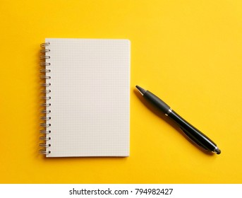 notebook,pen, on yellow background. top view copy space