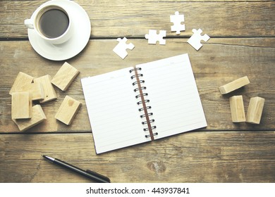 notebook,puzzle,wooden blocks and coffee on wooden table