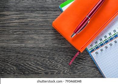 Notebooks biro pen on wood board top view.