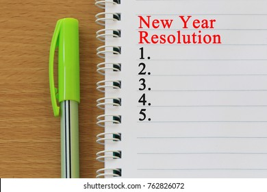 Notebooks and New year Resolution text  are placed on a brown wooden floor and have copy space for design in your work.