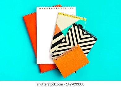 Notebooks. A lot of note pads with bright covers in one pile isolated on blue background. Design element, paper and leather texture. Colorful note pads on the shelf Top view Flat lay