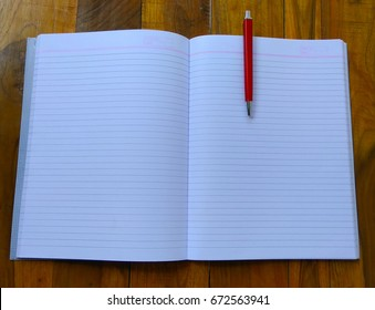Notebooks, pens on wooden background