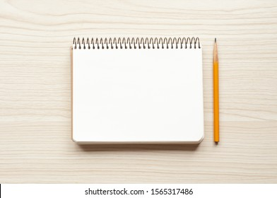Notepad with blank page and yellow pencil on wooden background. Notepad or notebook top view. Sketchbook with empty page. Photo image.