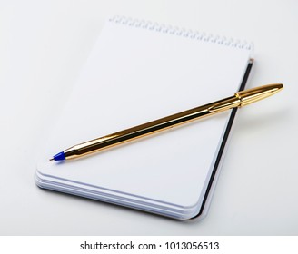 Notepad with blank paper next to golden ball pen on white background. Isolated. Mockup.