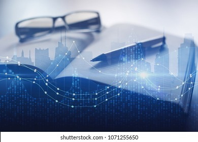 Notepad, blurry glasses and pen on abstract city background with glowing forex chart. Fund management and workplace concept. Double exposure