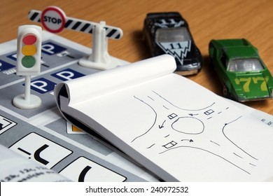 Notepad, book of traffic rules, toy cars, traffic lights and stop sign on a desk table. Studying and preparing for driving test