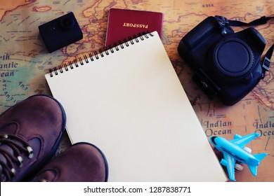 Notepad, camera , airplane miniature, passport, action camera and outdoor shoes. Selective focus. Adventurer set.