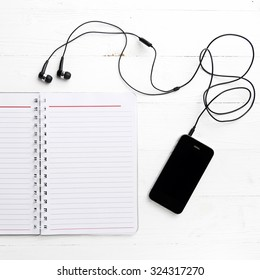 notepad and cellphone over white table