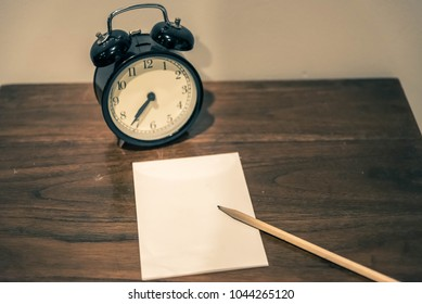 Notepad and clock on white board background as concept with copy space and note.