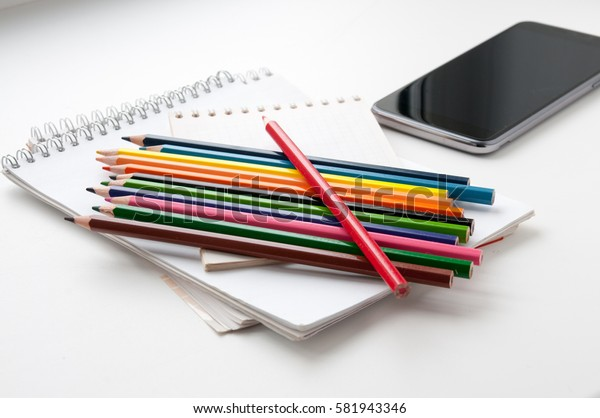 Notepad, color pencils and a phone on a light background