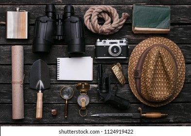 Notepad, compass, binoculars, film photo camera, loupe, dagger, handgun, diary book, shovel, rope, gold ore and old scroll document on adventurer or explorer wooden table. Traveler.