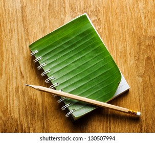 Notepad with cover of leaf lies on wooden board.