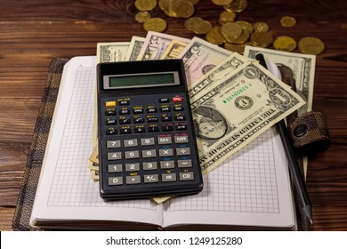 Notepad with dollars, pencil and calculator on wooden desk. Financial planning concept