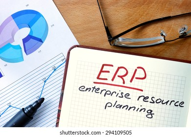 Notepad with Enterprise Resource Planning System (ERP) on office wooden table.