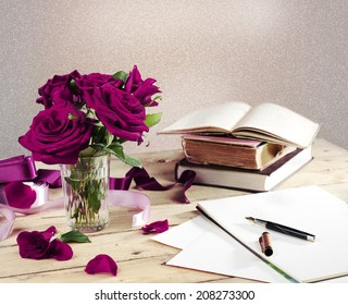 Notepad with fountain pen, red roses in a glass and old books on wooden desk in a vintage style