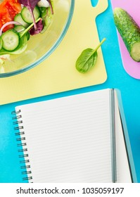 Notepad with fresh biodynamic ingredients for cooking summer salad on blue background, top view. Healthy food background