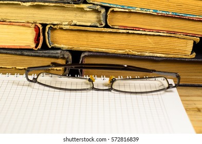 Notepad and glasses in front of many books