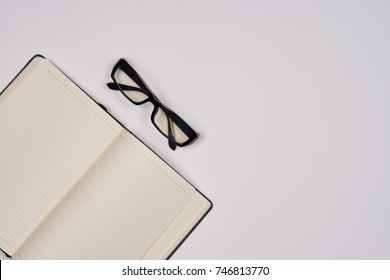 notepad, glasses on a light background, top view