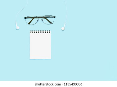 Notepad with glasses and various School or office accessories on blue table. Business or study concept. Top view, flat lay. Copyspace for your text.
