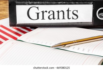 """Notepad with graphs and folder labeled """"Grants"""""""