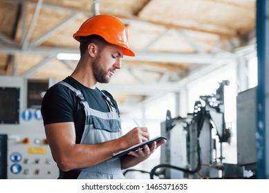 Mit Notizblock in der Hand. Industriearbeiter in Fabriken. Junge Technikerin mit orangefarbenem Hut.