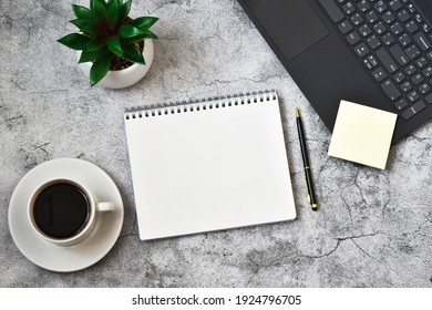 Notepad, laptop with cup coffee and pen on concrete grey background. Workplace. copy space, flat lay. Concept business and finance.