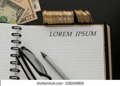 Notepad with Lorem ipsum words, pencil, glasses and dollar banknotes, stacks of coins on the background.