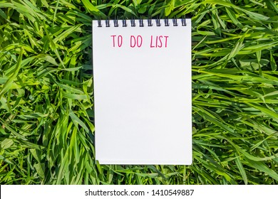"""Notepad is lying on the green grass. Summer bright sunny cozy still life. In the notebook, the inscription marker """"To do list""""."""