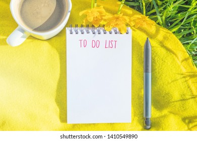 """Notepad is lying on the green grass. Summer bright sunny cozy still life. In the notebook, the inscription marker """"To do list"""".  A notebook lies on the rug, next is a cup of coffee, a pencil, flowers."""