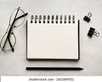 Notepad lying on a wooden table. Close-up, view from above, wooden surface. Concept of preparation for a professional holiday. Congratulations for relatives, friends and colleagues