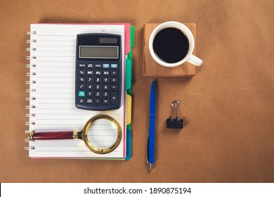 notepad with magnifier and calculator with coffee on table