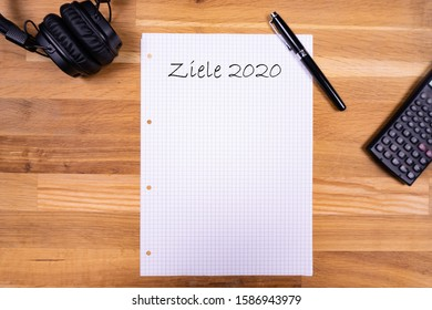 "A notepad with a note saying ""Ziele 2020"" (German for goals) together with a pen, a calculator and headphones on a wooden table - flat lay"