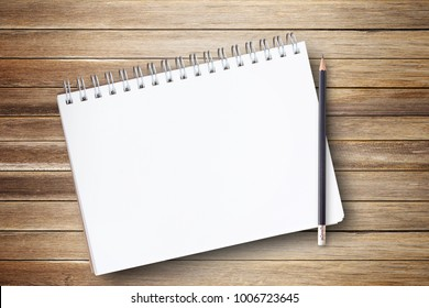 Notepad or notebook with pencil on brown wood table background.using wallpaper for education, business photo.Take note of the product for book with paper and concept, object or copy space.