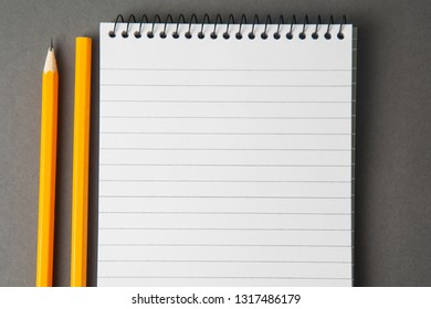 Notepad or notebook with pencil on gray background. Concept for education, business with copy space. Mock up.