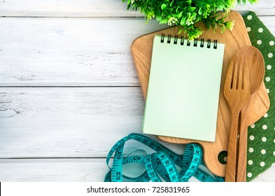 Notepad on chopping board with wooden fork and spoon and the measuring tape on white table , recipes food or diet plan for healthy habits shot note background concept