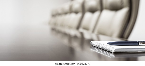 Notepad on table in empty conference room with copy space