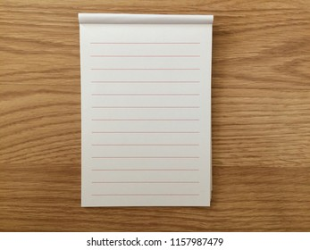 notepad is on wooden table. blank form. can be used montage for your text