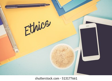 Notepad on workplace table and written ETHICS concept