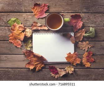 notepad open, mug with tea and autumn leaves on a wooden background. vintage toned. flat lay