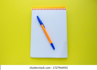 Notepad with an orange spiral and an orange pen, on a yellow background. top view copy space