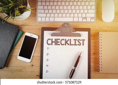 Notepad with a paper written CHECKLIST on wooden office desk with flare effect