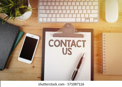 Notepad with a paper written CONTACT US on wooden office desk with flare effect