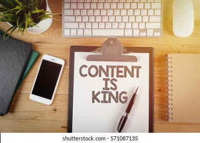 Notepad with a paper written CONTENT IS KING on wooden office desk with flare effect