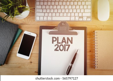 Notepad with a paper written PLAN 2017 on wooden office desk with flare effect