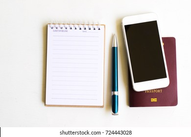 Notepad with passport and smartphone on wood board background.using wallpaper for education, business photo.Take note of the product for book with paper and concept, object or copy space.