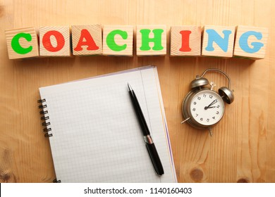 Notepad with pen and alarm clock on wooden background. Concept coaching. Top view